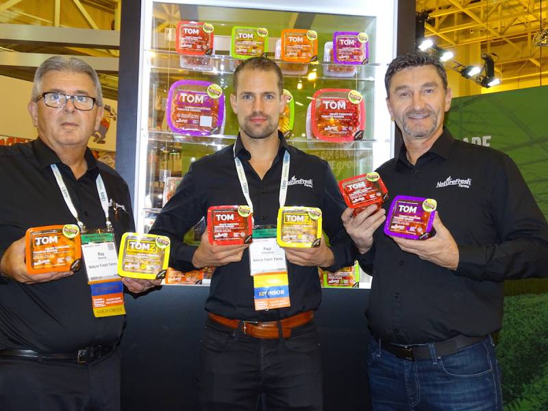 Paul Schockman (center) shows off TOMZ Snacking Tomatoes line from NatureFresh Farms at the PMA Show with Ray Wowryk on the left and Peter Quiring and the right